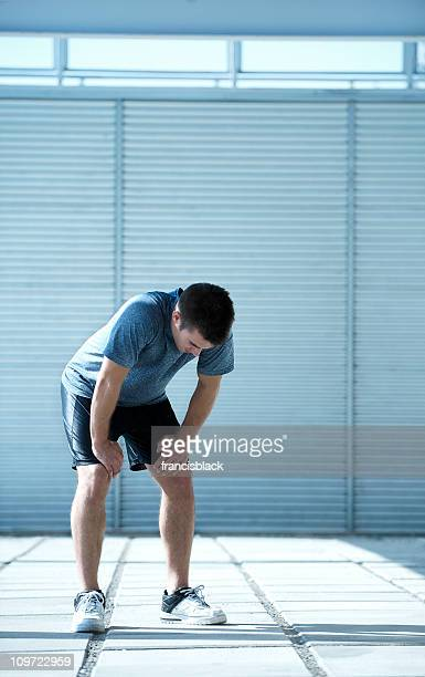 Exhausted athlete catching his breath after exercise