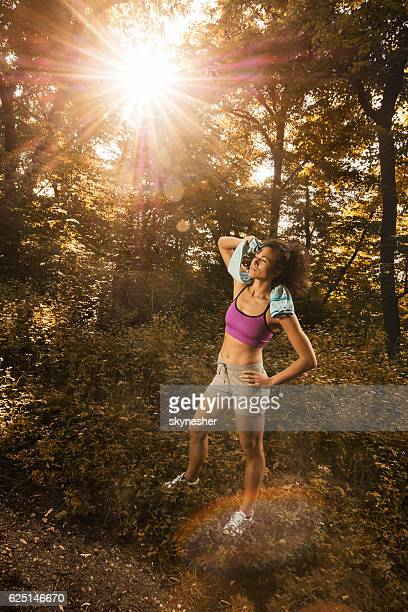 Exhausted athletic woman in nature wiping sweat of her forehead.