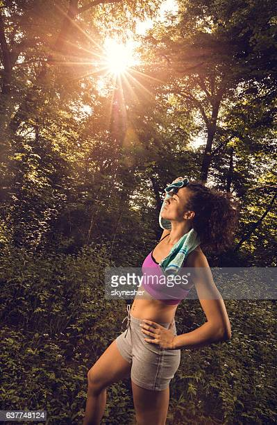 Exhausted athletic woman wiping sweat after exercising in nature.