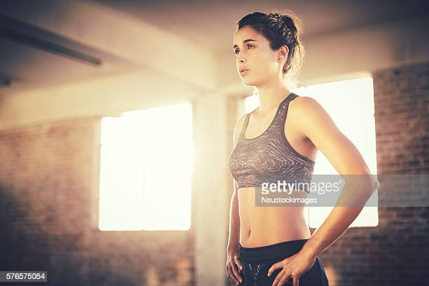 Exhausted attractive female with hands on hips in gym