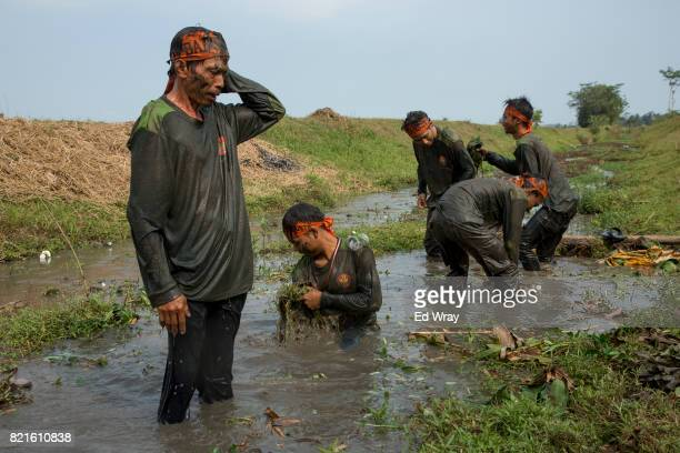 Exhausted Banser recruits wash themselves in an irrigation canal during a rigorous three day induction course on July 23 2017 in Kebumen Indonesia...