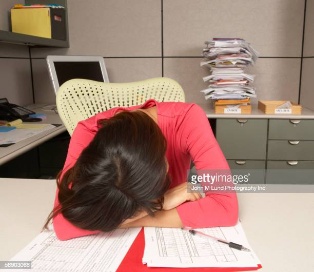 Exhausted businesswoman sleeping at desk
