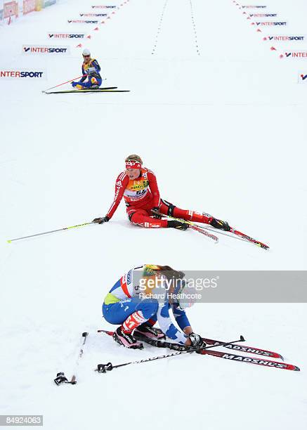 Exhausted competitors lie on the snow after crossing the finish line during the Ladies Cross Country 10km Individual Classic race at the FIS Nordic...