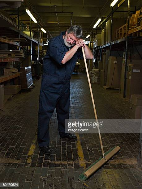 Exhausted man leaning on a broom