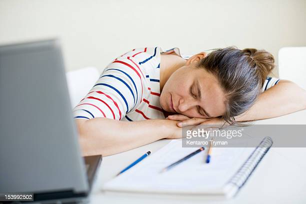 Exhausted mid adult woman sleeping at table with laptop