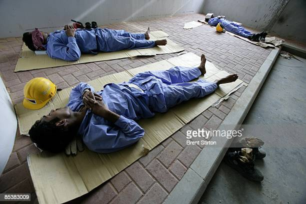 Exhausted migrant construction labourers working in Dubai take advantage of a break to get some sleep on May 1 2006 in Dubai United Arab Emirates...
