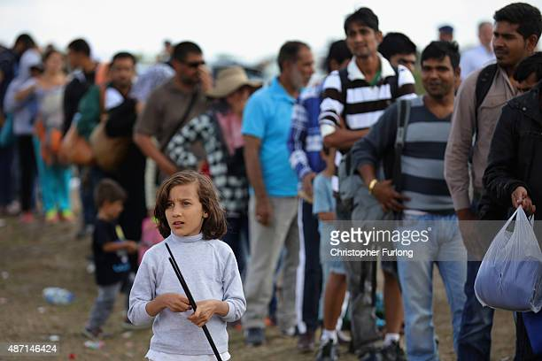 Exhausted migrants queue up in a holding area for food and water after crossing the border from Serbia into Hungary along the railway tracks close to...