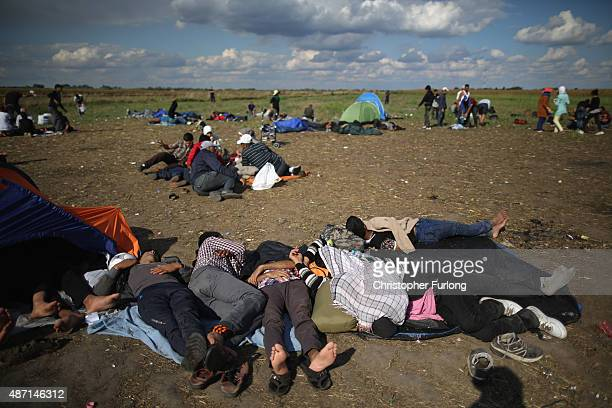 Exhausted migrants rest in a holding area after crossing the border from Serbia into Hungary along the railway tracks close to the village of Roszke...