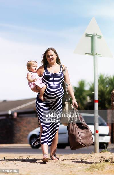 Exhausted overburdened pregnant woman carrying toddler and shopping bags