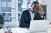 Feeling headache. Tired young serious african businessman is sitting at desk and touching his head while expressing weariness. He is looking at screen of modern laptop with concentration. Copy space