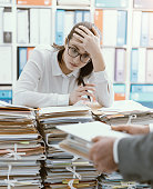 Exhausted young secretary overloaded with work, her boss is bringing more paperwork to her