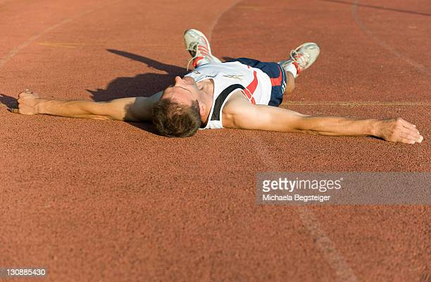 Exhausted sportsman lying on running track