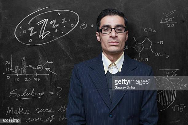 Exhausted teacher feeling sleepy in classroom standing against blackboard.