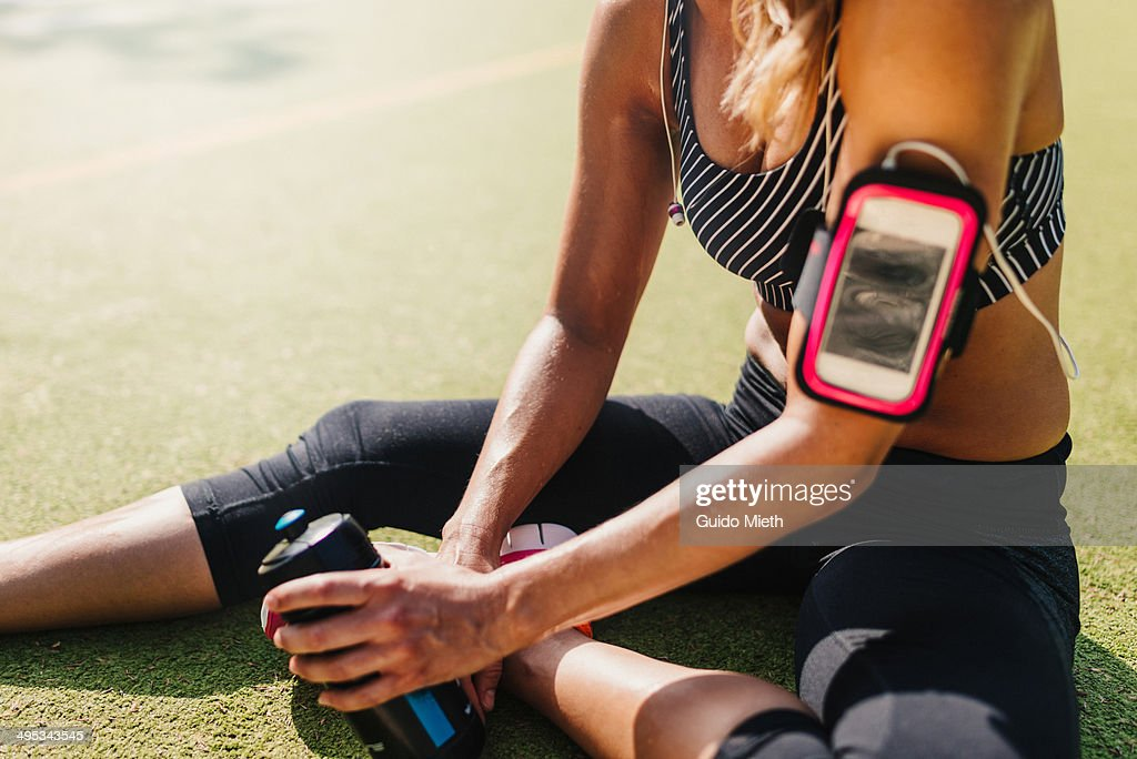 Exhausted woman relaxing on sports field. : Stock Photo