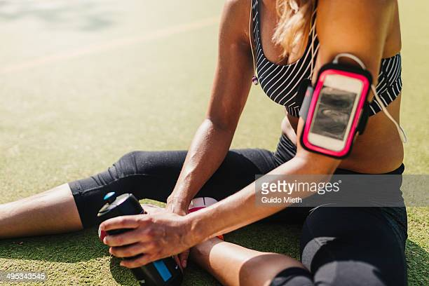 Exhausted woman relaxing on sports field.