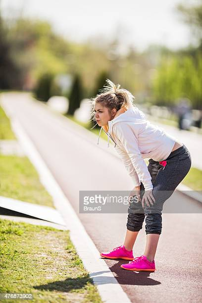 Exhausted woman taking a breath after jogging.