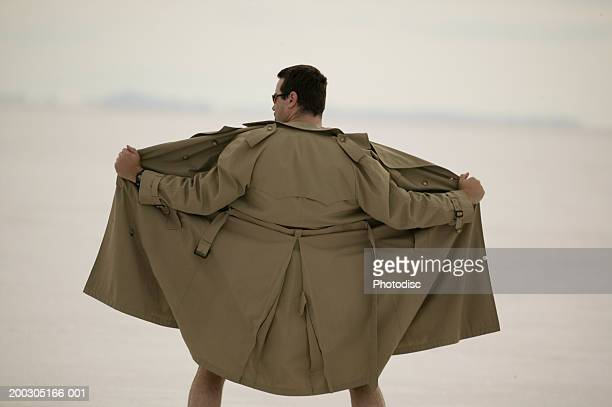 Exhibitionist spreading front of coat, at beach