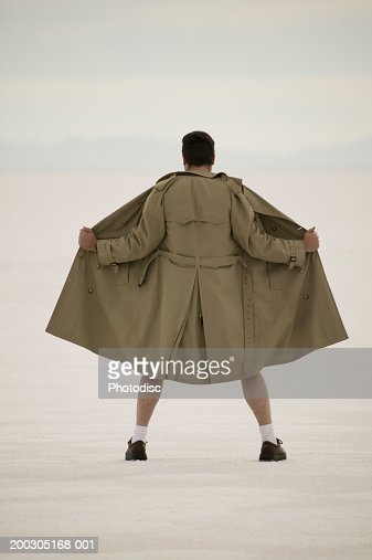 Exhibitionist spreading front of coat, at beach : Stock-Foto