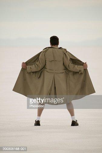Exhibitionist spreading front of coat, at beach : Foto de stock