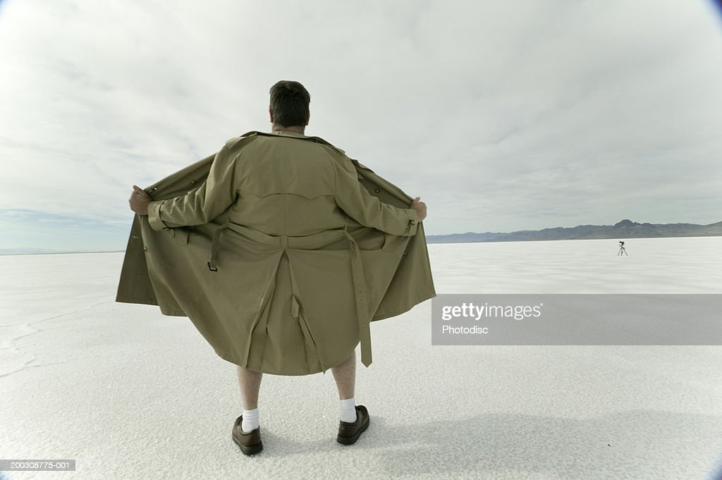 Exhibitionist spreading open coat in desert : Stock Photo