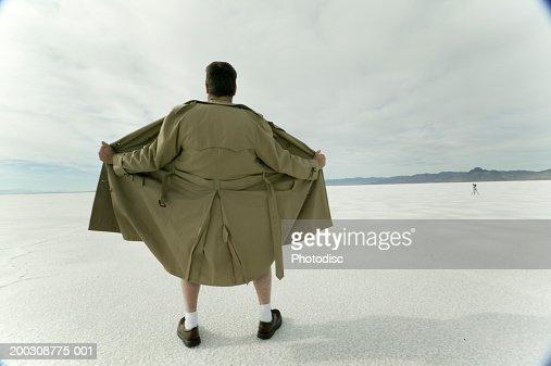 Exhibitionist spreading open coat in desert