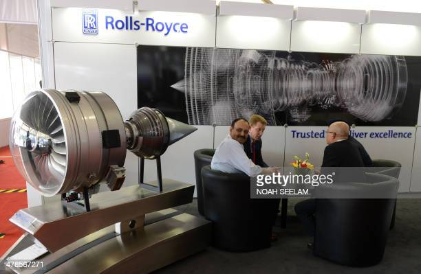 Exhibitors and delegates speak as they sit near a model of a Trent 1000 Mark Aircraft engine which is used for the Boeing 787 Dreamliner on display...