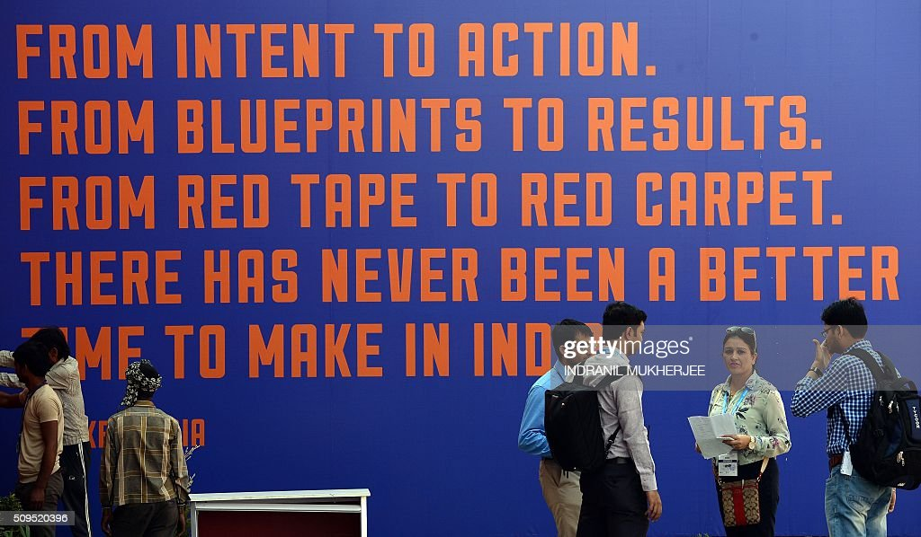 Exhibitors and staff interact in front of a slogan at the venue for the 'Make in India' showcase week in Mumbai on February 11, 2016. Over 190 companies, including national conglomerates and multinational corporations, 5,000 delegates from 60 countries, and leading industrialists including Ratan Tata and Mukesh Ambani will be participating in the maiden 'Make in India' showcase to be held in Mumbai from February 13-18. AFP PHOTO/ INDRANIL MUKHERJEE / AFP / INDRANIL MUKHERJEE