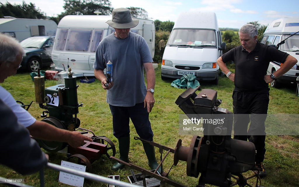 Exhibitors gather around stationary engines being shown at the Cornish Steam and Country Fair at the Stithians Showground on August 16, 2013 near Penryn, England. The annual show, now in 58th year, is one of Cornwall's largest outdoor events and is one of the UK's most popular and respected steam rallies.
