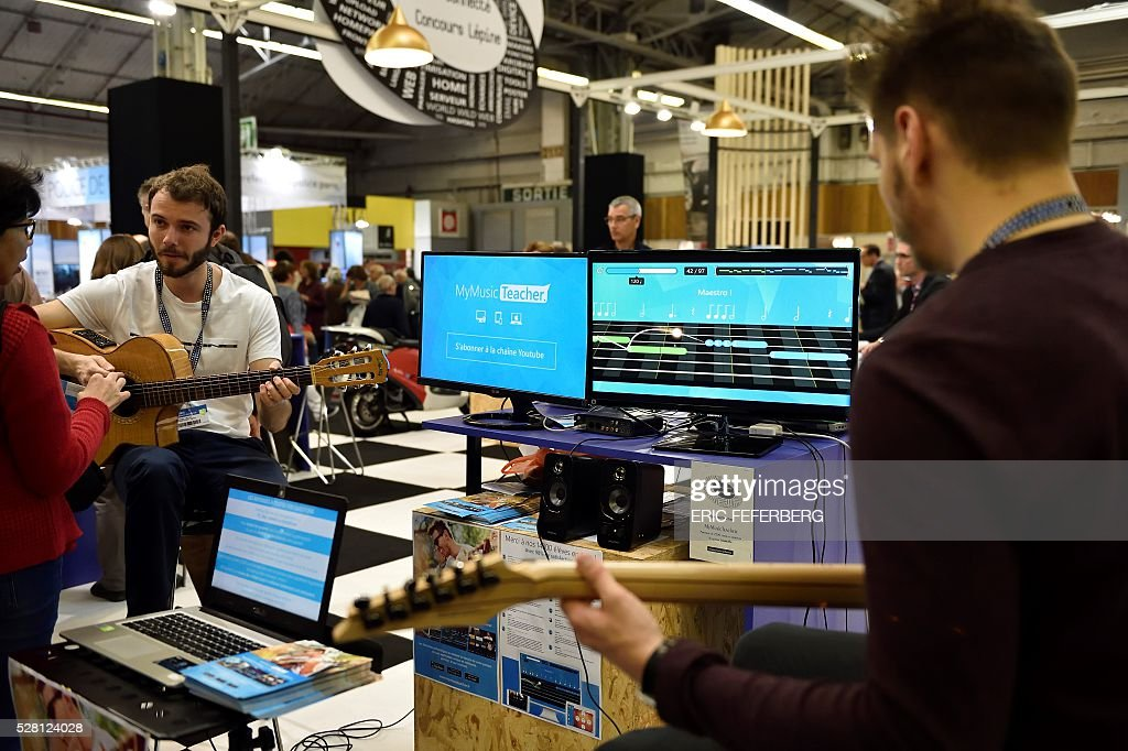 Exhibitors present 'My Music Teacher' music learning software at a stand of the 'Concours Lepine' (Lepine contest) at Paris' fair, on May 4, 2016 in Paris. The Lepine contest, a competition for inventors in the world, was launched in 1901 by Louis Lepine, the city's police chief and has chalked up some notable successes, such as the world's first artificial heart in 1937. / AFP / ERIC