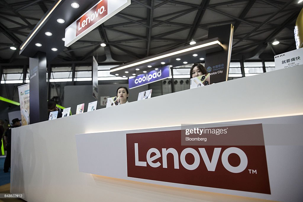 Exhibitors sit behind a counter at the Lenovo Group Ltd. booth at the Mobile World Congress Shanghai in Shanghai, China, on Wednesday, June 29, 2016. The exhibition runs until July 1. Photographer: Qilai Shen/Bloomberg via Getty Images