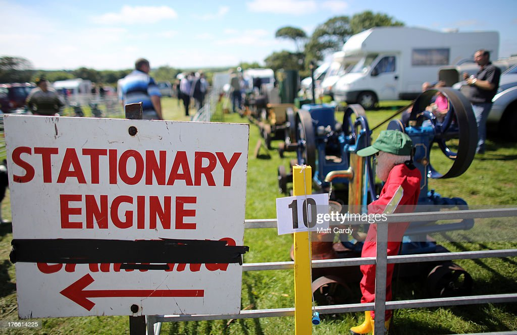 Exhibitors sits besides their stationary engines being shown at the Cornish Steam and Country Fair at the Stithians Showground on August 16, 2013 near Penryn, England. The annual show, now in 58th year, is one of Cornwall's largest outdoor events and is one of the UK's most popular and respected steam rallies.