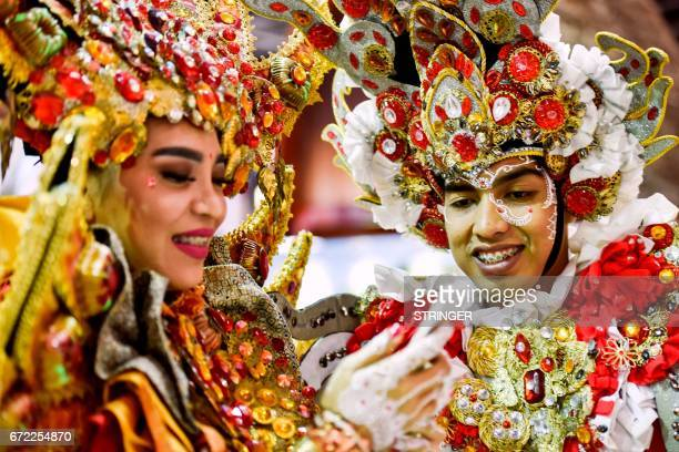 Exhibitors wearing traditional costumes stand at the Indonesia pavilion during the Arabian Travel Market 2017 at the Dubai World Trade Centre on...