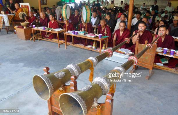 Exile Tibetan Buddhist monks blow ceremonial horns during a special morning prayer session as they celebrate the 82nd birthday of their spiritual...