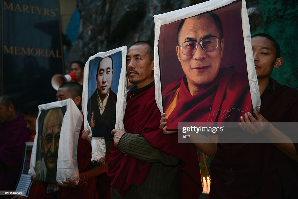 Exile Tibetans carry portraits of the Dalai Lama (R), the late Panchen Lama (C), and Indian independence icon Mahatma Gandhi (L) during a candlelight vigil to mourn the deaths of self-immolators in protest against Chinese rule in Tibet, in Dharamsala on February 25, 2013. Two Tibetans, identified as Tsezung Kyap, 27, and Sangdak, 19, reportedly self-immolated February 25 according to Tibetan rights groups. More than 100 people have set themselves on fire in protest at China's rule since 2009, at least 85 of whom have died, according to reports. AFP PHOTO/LOBSANG WANGYAL