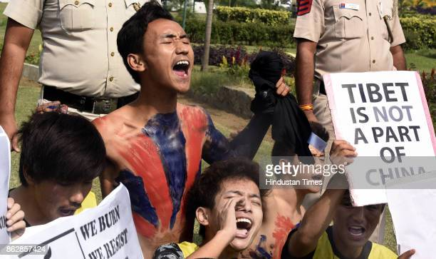 Exile Tibetans shout slogans as police detain them during a protest near the Chinese embassy on October 18 2017 in New Delhi India Nearly two dozen...