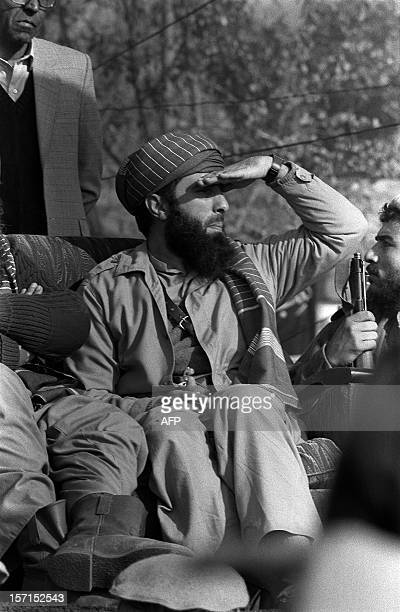 Exiled Afghan warlord Gulbuddin Hekmatyar protects his eyes from bright sun while looking at crowd of Afghan mujahedeen who gathered 17 January 1987...