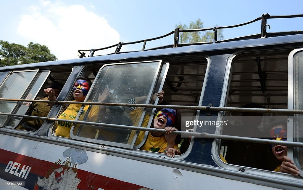 Exiled Tibetan activists shouts anti-China slogans from a police bus at the Chanakyapuri police station following their arrest for protesting outside the Chinese Embassy to mark the 55th anniversary of the 1959 Tibetan uprising against Chinese rule in New Delhi on March 12, 2014. Tibetan anger at Beijing's control simmered for decades and erupted into violent riots against Chinese rule in the Tibet regional capital Lhasa and adjacent areas in March 2008. Since 2009, more than 120 Tibetans have set themselves on fire to protest at China's rule and at least 90 have died. AFP PHOTO/Chandan KHANNA
