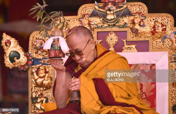 Exiled Tibetan spiritual leader the Dalai Lama performs a ritual as he speaks at the Yiga Choezin ground in the district of Tawang in India's...