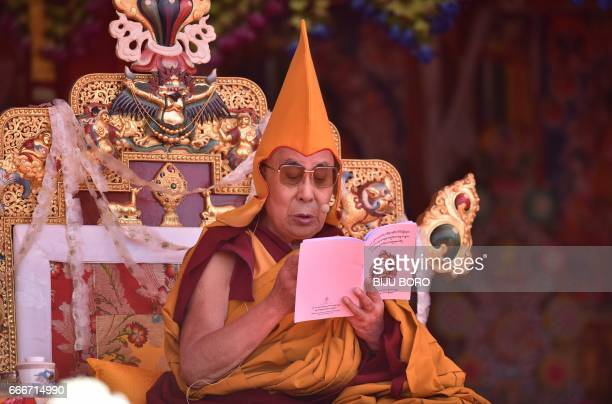 Exiled Tibetan spiritual leader the Dalai Lama reads from a religious book on the last day of his visit at the Yiga Choezin ground in Tawang District...