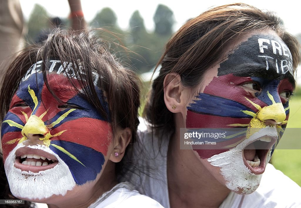 Exiled Tibetan women with their faces painted in the colors of a Tibetan flag shout slogans from inside a bus after they were detained during a protest to mark the women uprising day on March 12, 2013 in New Delhi, India.