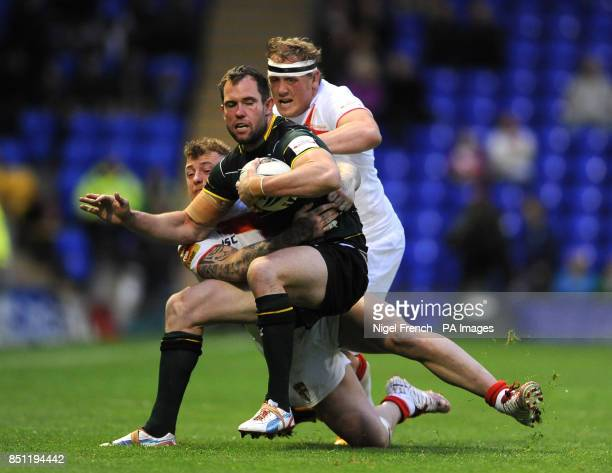 Exiles Pat Richards is tackled by England's Josh Charnley and Ben Westwood during the Interational match at the Halliwell Jones Stadium Warrington