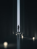 Young woman in a dark, narrow corridor, walking towards the unknown. She is holding a bunch of lit lightbulbs in her arms