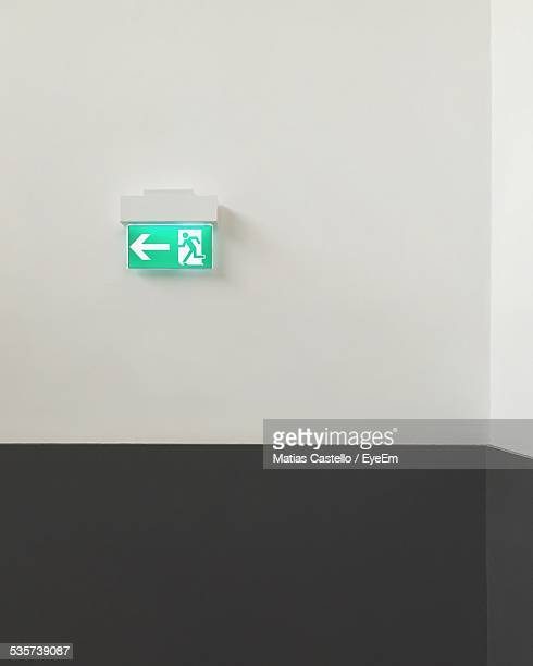 Exit Sign And Arrow Symbol On Wall