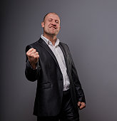 Exited bald business man in black suit showing the hands success winner sign on grey background. Closeup portrait