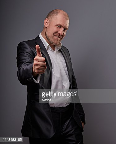 Exited comic bald business man in black suit showing the finger success thumb up sign on grey background. Closeup : Stock Photo