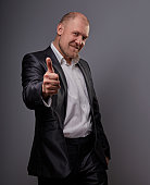 Exited comic bald business man in black suit showing the finger success thumb up sign on grey background. Closeup portrait