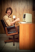 A vintage retro styled image with brown tones of a man in a wood paneled 1980s room sitting at his computer desk with a coffee cup in hand smiling