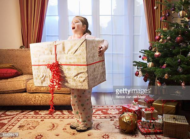 Exited girl holding large present.
