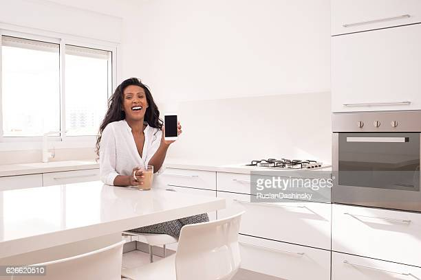 Exited woman showing cellphone, sitting at kitchen.