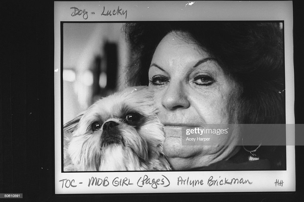 Ex-mob girl Arlyne Brickman who was an informant for the FBI on several members of the Mafia, snuggling w. her Lhasa apso dog; she refuses to participate in the Witness Protection Program.